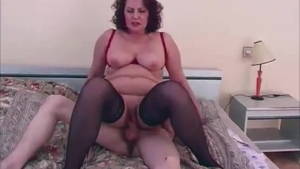 Beautiful granny is wearing sexy, black stockings while riding a hard dick in her home